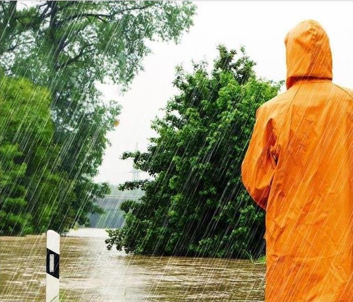 Person standing in the rain wearing a rain jacket looking at a flooded street.
